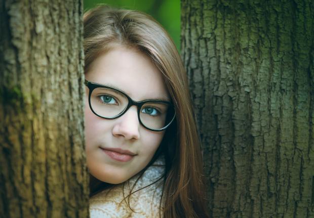 девушка в очках между деревьев