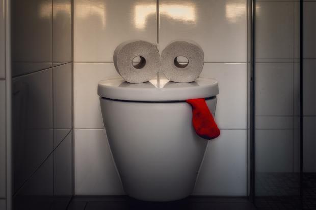 инсталляция из унитаза с туалетной бумагой и красным носком