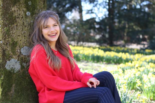 девушка в красном свитере сидит под деревом