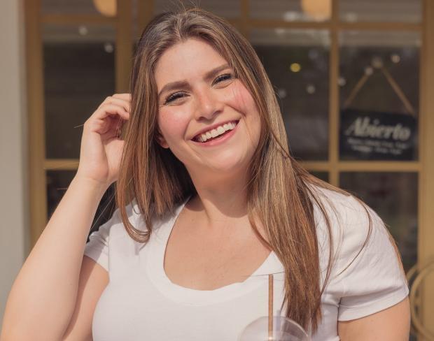 улыбающаяся девушка с длинными волосами в белой футболке