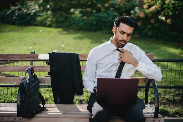 молодой мужчина в белой рубашке и черных брюках сидит на лавке с компьютером