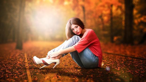 девушка в джинсах и красном джемпере сидит на засыпанном листьями асфальте