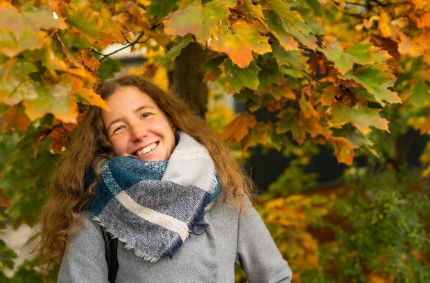 девушка в клетчатом шарфе и сером пальто смеется на осенней аллее