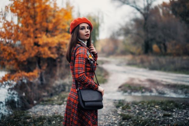 девушка в красном клетчатом пальто и красном берете стоит на осенней аллее