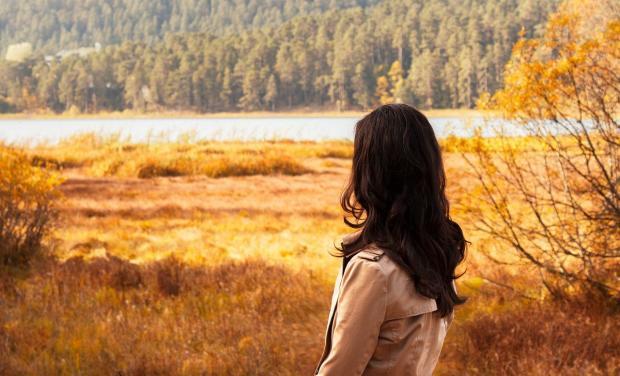 брюнетка смотрит на речку осенью