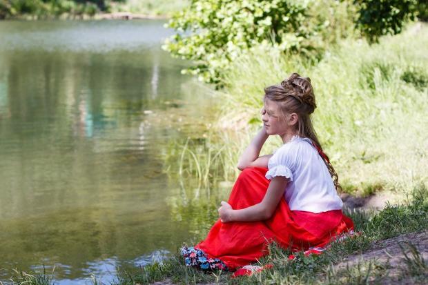 девушка в красной юбке сидит на берегу озера
