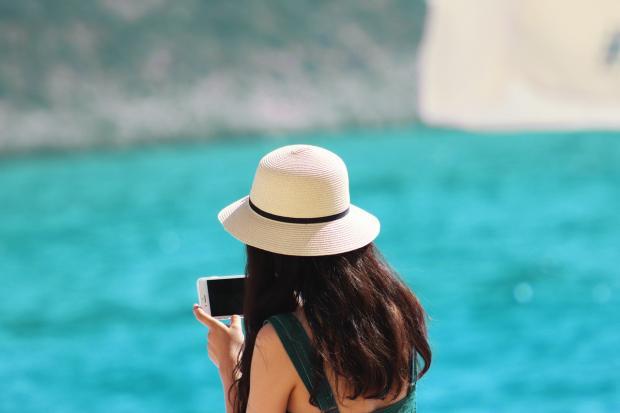 девушка в белой шляпе фотографирует море