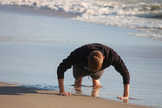 мужчина отжимается на берегу