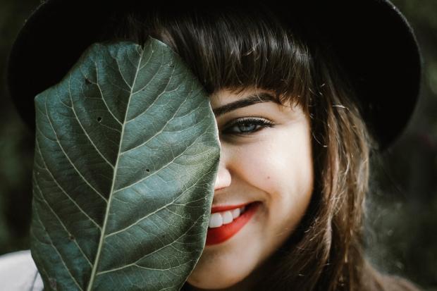 девушка с улыбкой скрыла половину листа за большим листом растения