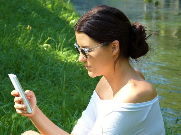девушка в белой футболке смотри на телефон на берегу реки
