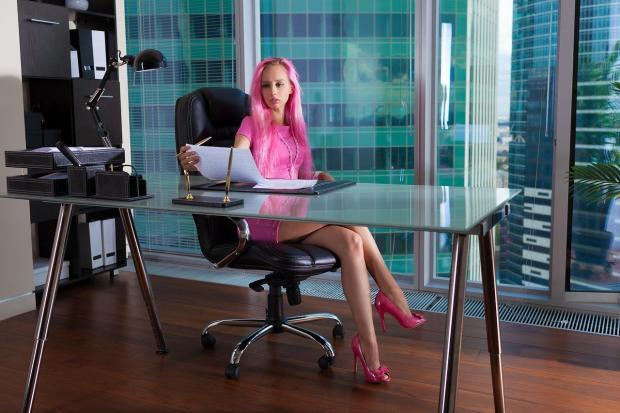 девушка с розовыми волосами и в розовом платье сидит за столом в офисе