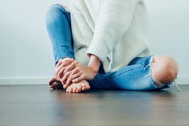 на полу сидит девушка в голубых джинсах с оголенным коленом