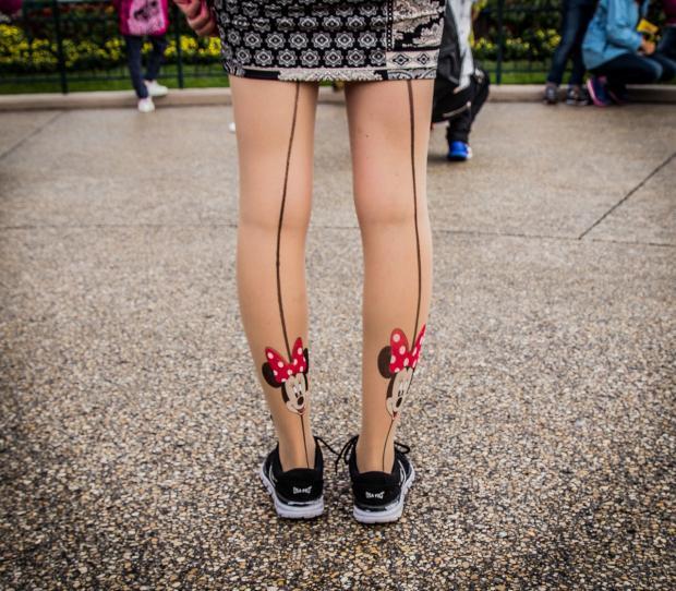 девушка стоит на асфальте в колготках с рисунком