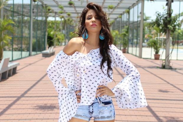 стоит девушка в джинсовых шортах и свободной белой блузке