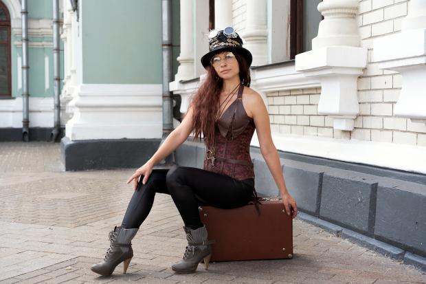 девушка в корсете и шляпе сидит на коричневом чемодане
