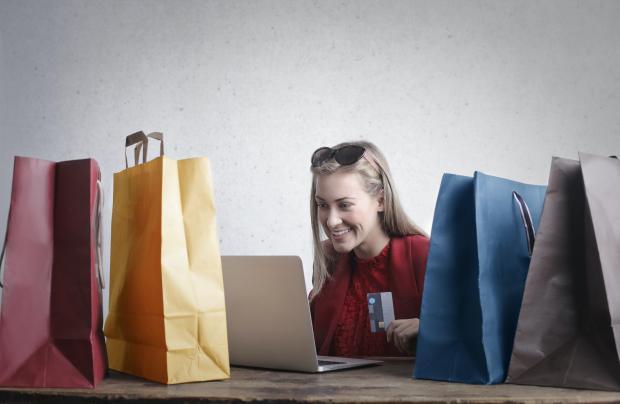 девушка с банковской картой, пакеты с покупками, ноутбук