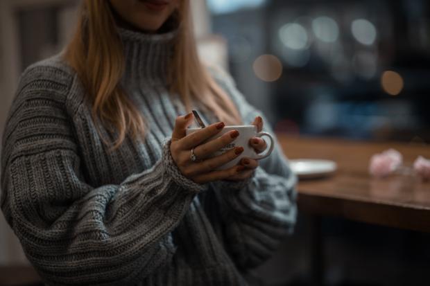 девушка в свитере с чашкой чая в руках