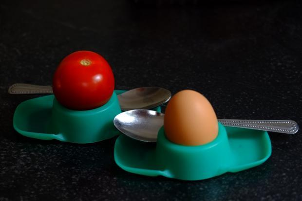 в подставке для яиц лежат яйцо и красный помидор