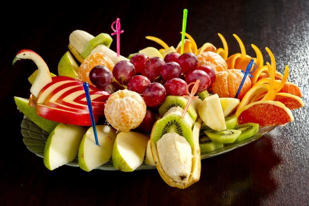 тарелка с нарезанными фруктами и ягодами