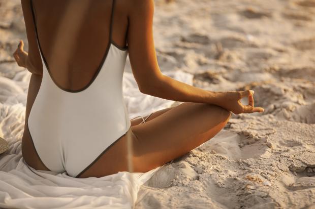 Девушка в белом купальнике осваивает технику дыхания йога на пляже