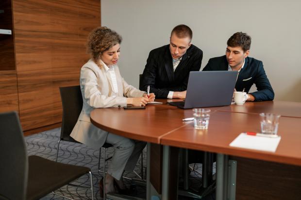 двое мужчин и женщина в офисе за столом