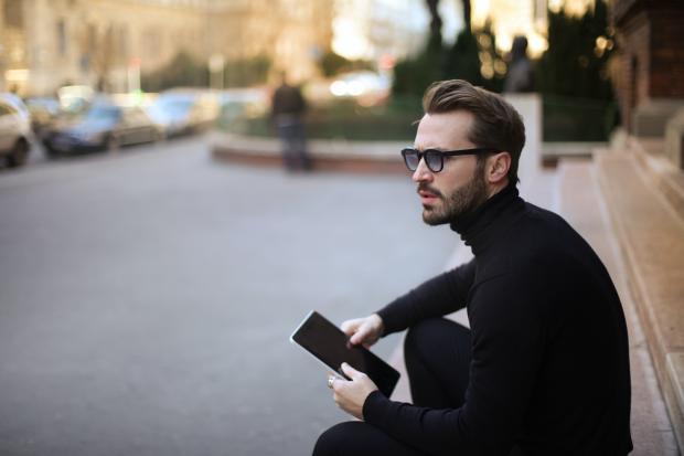 мужчина в очках сидит на ступеньках