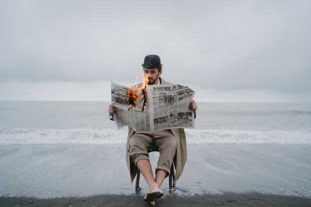 мужчина на стуле на берегу моря с горящей газетой в руках