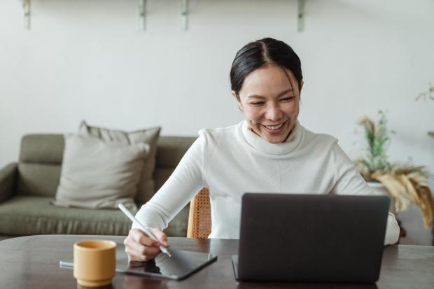 женщина работает за ноутбуком и планшетом
