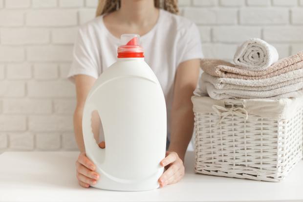 бутылка с кондиционером для белья, чистые полотенца