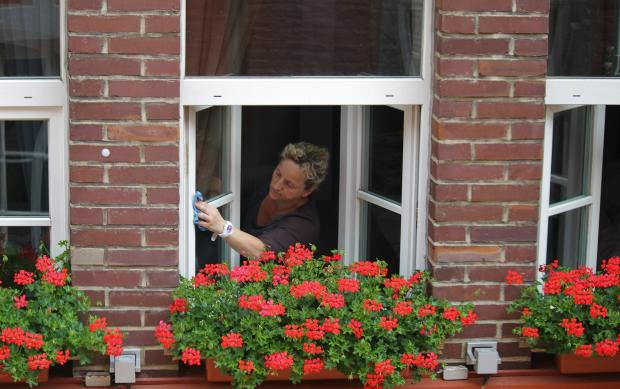 человек моет окна в доме