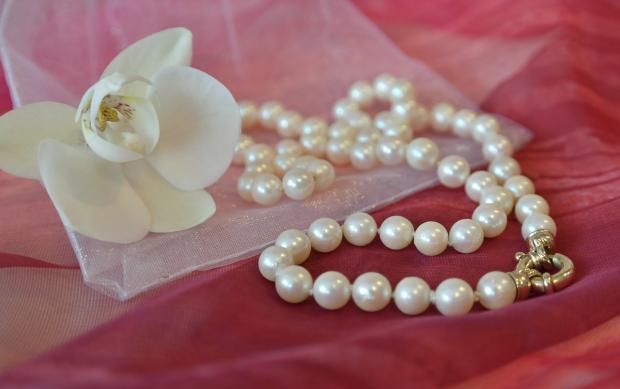 белое жемчужное ожерелье лежит на розовой ткани