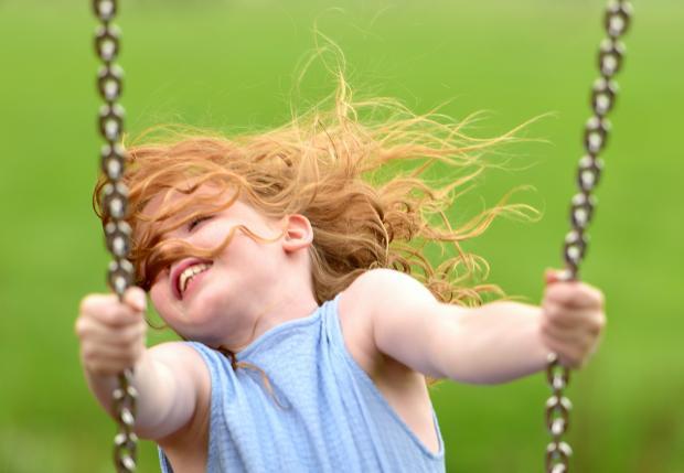 маленькая рыжеволосая девочка на качеле