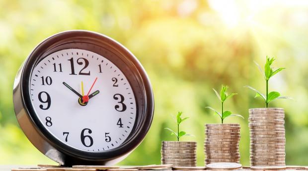 будильник и зеленые ростки из стопки монет