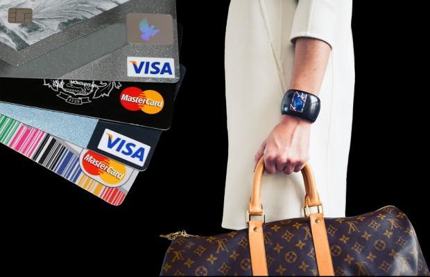 сумка для шопинга в руке на фоне пластиковых карт