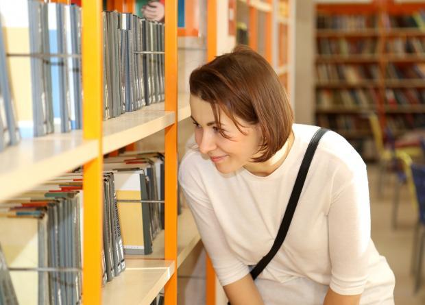 девушка рассматривает книги в библиотеке на полках