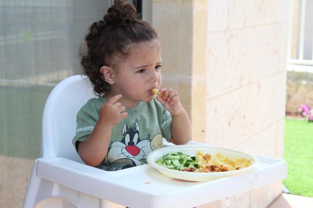 маленькая девочка на стульчике ест