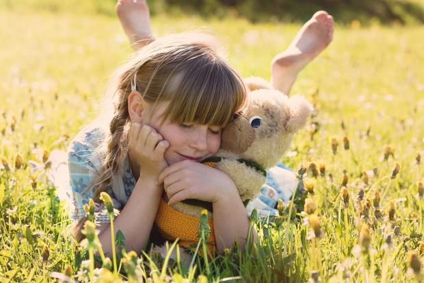 девушка с мишкой лежит в траве