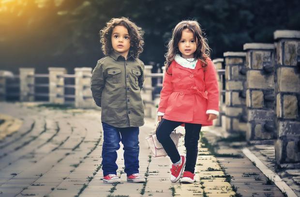 Маленькие мальчик и девочка гуляют на улице