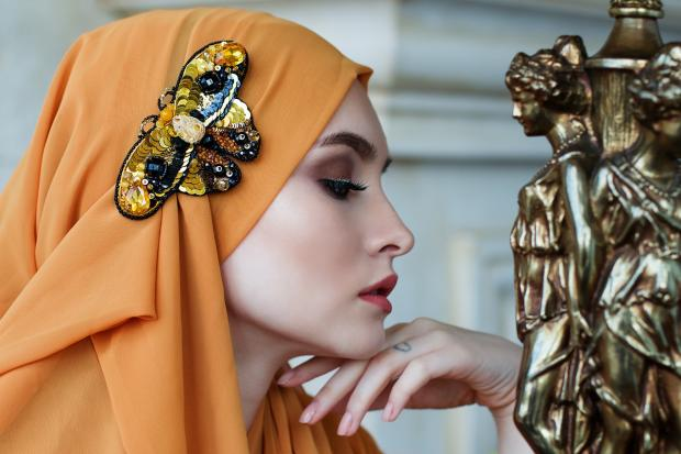 красивая девушка в платке с драгоценной брошью бабочкой