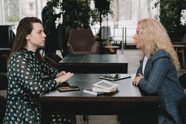 две женщины общаются за столом