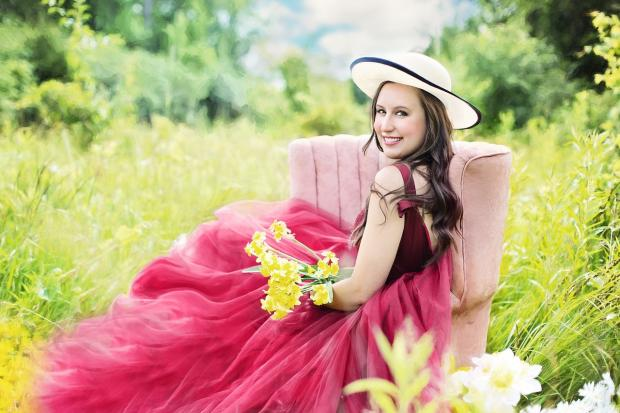 девушка в розовом платье и шляпке сидит в кресле на лугу