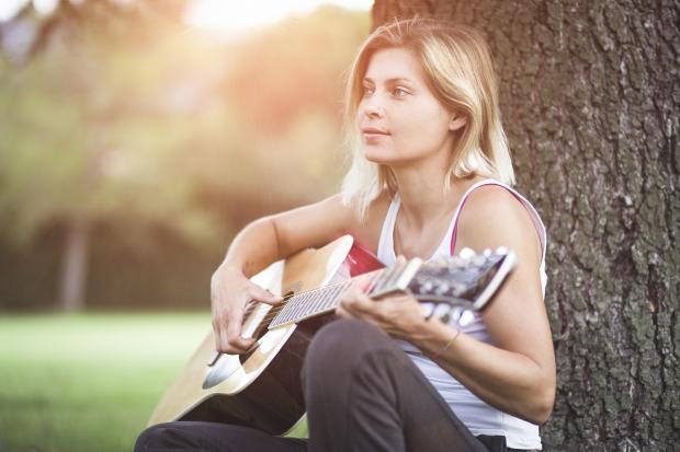 девушка играет на гитаре рядом со стволом большого дерева