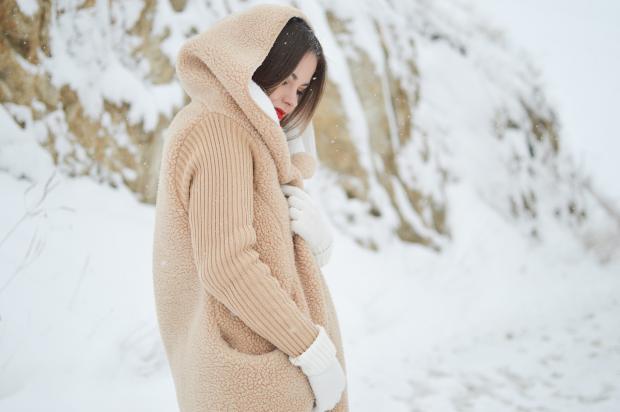 в горах стоит девушка в теплой кремовой куртке