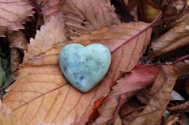 камень в форме сердца лежит на осенних листьях
