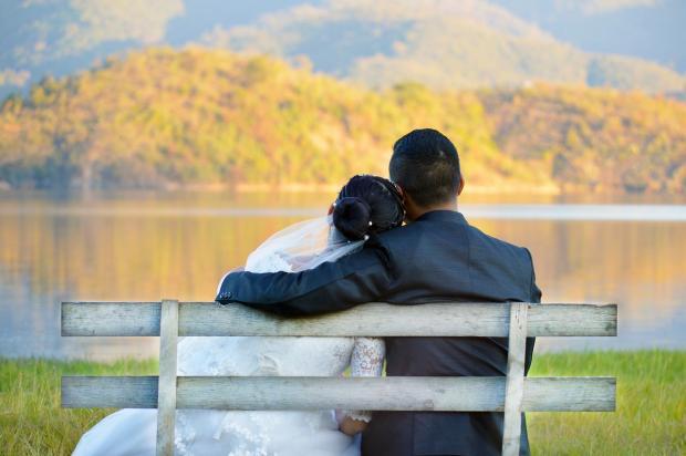 молодожены сидят на деревянной скамейке на берегу озера осенью