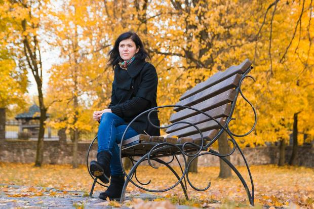 девушка в черном пальто и синих джинсах сидит на скамейке на осенней аллее