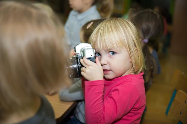 девочка с фотоаппаратом в детском саду