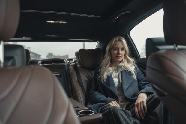 девушка-блондинка в деловом костюме в салоне автомобиля