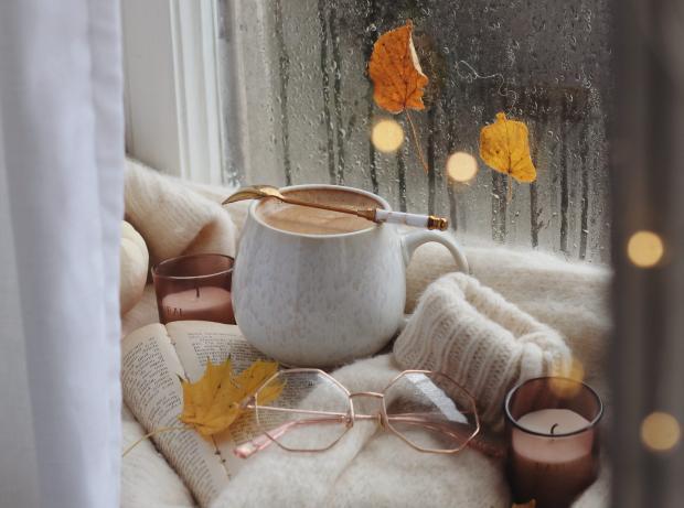 книга, очки, чашка с какао и свечи на подоконнике