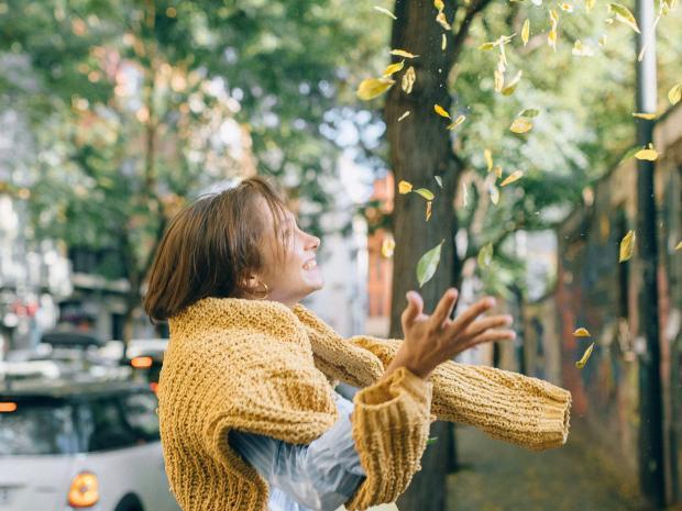девушка в теплом свитере бросает в воздух желтые листья